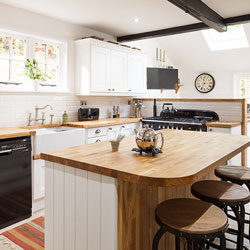A kitchen with white cupboards, wood worktops and contemporary features