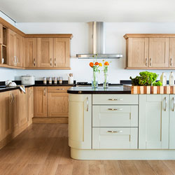 Wooden kitchen cabinets with a black worktop, and a green painted island