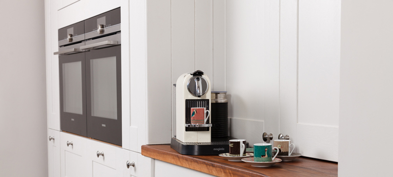 Two ovens and a ledge with coffee making facilities provide visual contrast to the whitewashed kitchen cabinets