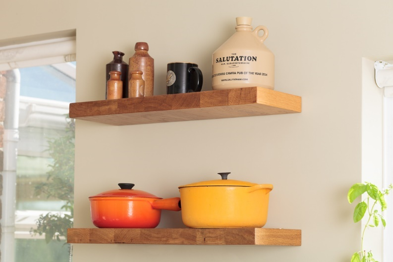 Brightly coloured casserole pans and decorative ornaments adorn floating shelves between two windows