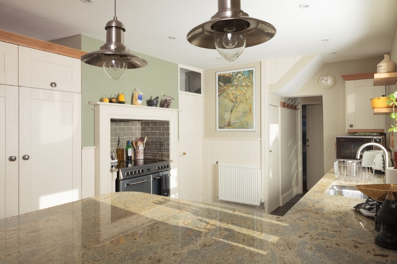 Industrial pendant lamps shine light over a massive peninsula worktop in this classic kitchen