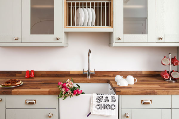 This kitchen features shaker cabinets in Farrow & Ball's mizzle with Walnut worktops and a Belfast sink