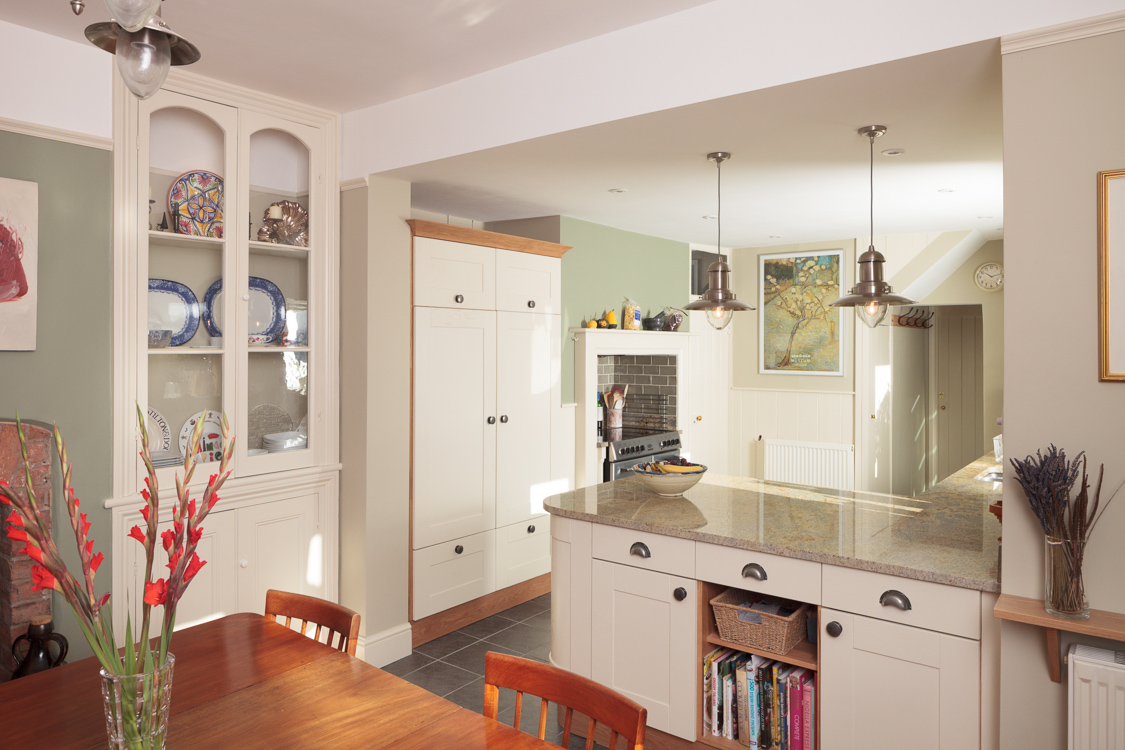 An open-plan kitchen and dining room with a full-height display cabinet