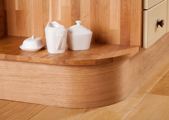 A curved solid oak plinth running under an open corner cabinet