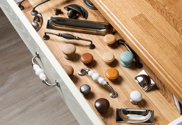 A selection of handles and knobs in a drawer under an oak worktop with ogee profiling