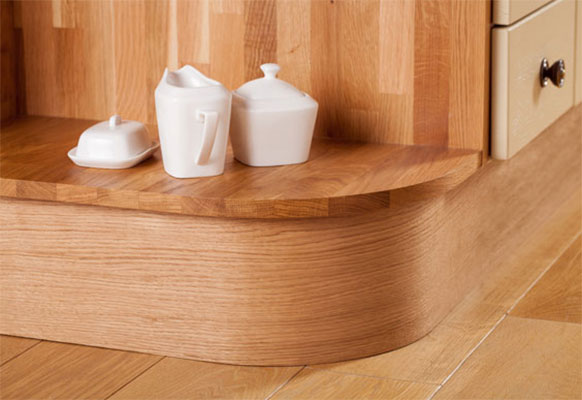 An open corner cabinet with a curved oak plinth