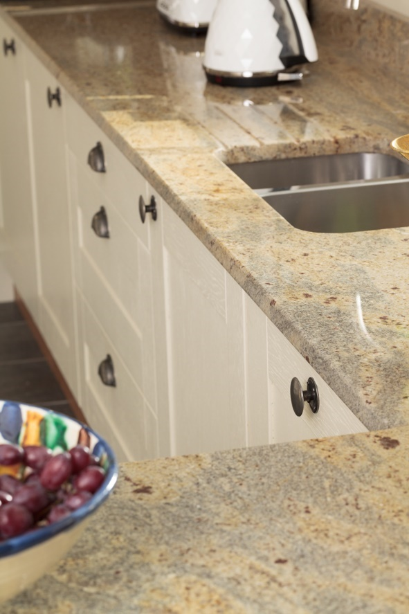 A stainless steel sink within a granite worktop in a classic kitchen