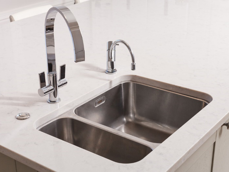 A contemporary stainless steel undermounted sink with one large and one smaller bowl