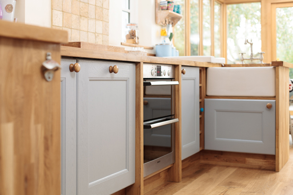 Traditional cabinet doors in Farrow & Ball's Parma Grey and oak end panels, plinths, pilasters and worktops